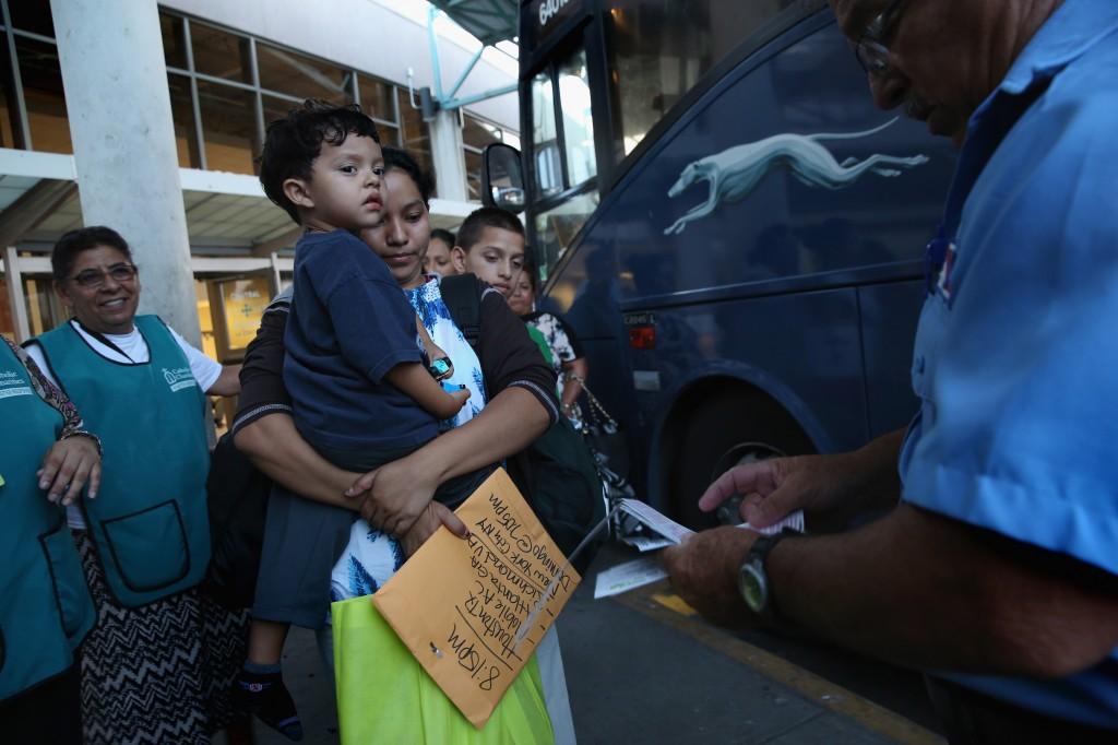 Volunteers escort families to their bus departure.