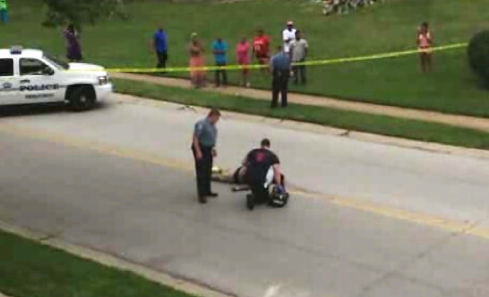"FILE - In this Saturday, Aug. 9, 2014 file image from TV provided by KMOV-TV, investigators inspect the body of Michael Brown, after he was shot, in Ferguson, Mo. Brown, who was fatally shot by police, suffered a bullet wound to his right arm that may have occurred when he put his hands up or when his back was turned to the shooter, ""but we don't know,"" a pathologist hired by the teen's family said Monday, Aug. 18, 2014. (AP Photo/KMOV-TV, Tiffany Mitchell, File)"