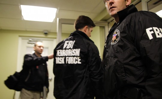 FBI Agents and members of the FBI Terrorism Task Force prepare for a pre-dawn raid on the home of a suspected terrorist.  Pittsburgh, Pennsylvania, 2012.