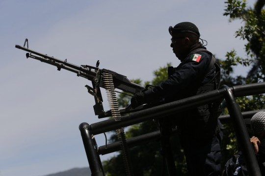 Image #: 32917288    A federal police rides atop a vehicle as he patrols on a road in town of Cocula near Iguala, in the southwestern state of Guerrero, November 2, 2014. Authorities on October 27, 2014 said they had arrested four drug gang members involved in the kidnapping of the 43 missing student teachers from the Ayotzinapa Teacher Training College Raul Isidro Burgos, who disappeared last month and are feared massacred. REUTERS/Henry Romero (MEXICO - Tags: CRIME LAW EDUCATION POLITICS CIVIL UNREST)       Reuters /HENRY ROMERO /LANDOV